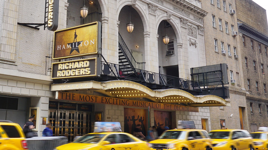 A single black star stands out from a golden poster, illuminated by marquee lights as yellow as the taxis driving by. Overlaid on top of the star in bold white letters: Hamilton: An American Musical.