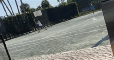 Sejong Kim, a 7th grader at OHS and a competitive tennis player, practices on the court.