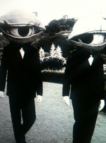 Vintage photograph featuring two individuals dressed as giant eyes courtesy of ancientfaces.com.